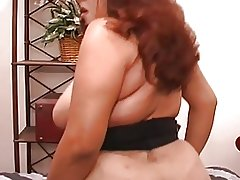 Curvy Latina rides dildo on dresser