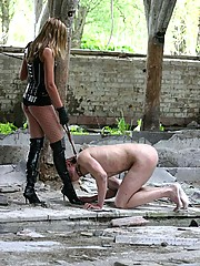 Latex mistress feeds her naked freak somewhere in ruines spitting chewed apple at him